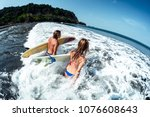 couple of surfers runs into... | Shutterstock . vector #1076608643
