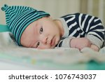 funny baby boy laying on the  ... | Shutterstock . vector #1076743037