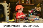 Small photo of Little helper in workshop. Side view kid playing with screw bolts. Boy busy learning how to work with different tools.