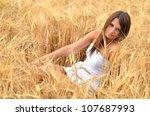 woman in golden wheat | Shutterstock . vector #107687993