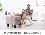 man with broken leg in cast... | Shutterstock . vector #1077030977