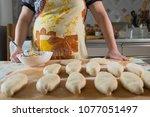 cooking. a woman puts a pie... | Shutterstock . vector #1077051497