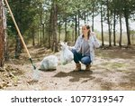 young woman cleaning rubbish... | Shutterstock . vector #1077319547