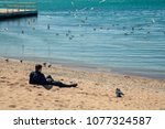 young man on the beach   | Shutterstock . vector #1077324587