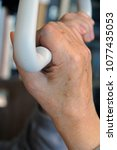 old man's hand on a trapeze | Shutterstock . vector #1077435053