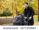 man walks with perambulator in... | Shutterstock . vector #1077453863