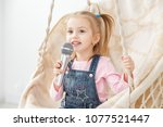 a little cheerful girl sings a...   Shutterstock . vector #1077521447