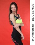 girl in overalls posing on red...   Shutterstock . vector #1077687503