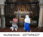 Small photo of Bari/Italy - 05/23/2016. Basilica di San Nicola. People kneel and pray before the tomb of St. Nicholas.