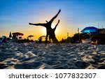 young couple makes handstand at ... | Shutterstock . vector #1077832307