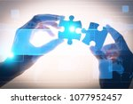 pieces of jigsaw puzzle in hands | Shutterstock . vector #1077952457