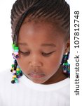 Cute and pretty African American little girl wearing white top and her hair braided and plaited with colorful beads looking down sadly and upset - stock photo