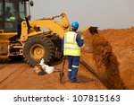 African American construction site worker wearing blue overalls and yellow high visibility safety jacket standing and watching bucket digger digging trench on sandy rocky land - stock photo