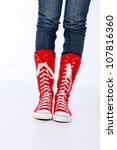 Trendy funky female or male hi top red canvas and white rubber boxing style trainer boots worn with blue jeans and both feet facing forwards - stock photo