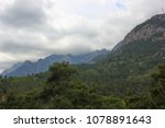 Small photo of mountains near which thickened gloomy clouds, lots of green trees, conifers, countryside landscape
