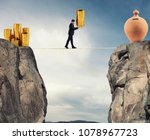 Small photo of Businessman moves a pile of coins to a moneybox. concept of difficulty to saving money