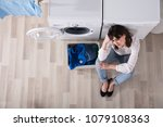upset woman sitting at laundry... | Shutterstock . vector #1079108363
