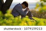 Small photo of young man praying to God near a tree in the nature bowing his head to his knees with gratitude, male asks for help finding solace in faith, concept religion