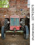 A red and green antique tractor - stock photo