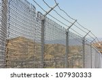 Focus is on the fence with a suburb neighborhood in the far distance. - stock photo