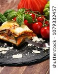 Small photo of Serving of spicy traditional Italian beef lasagne in a restaurant - bolognese sauce topped with basil leafs