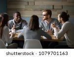 Small photo of Multiracial young friends talking drinking coffee together sitting at cafe table, african man telling joke while diverse millennial smiling people enjoying listening having fun at coffeehouse meeting