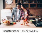 couple looks at a recipe in... | Shutterstock . vector #1079768117