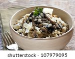 Bowl of mushroom risotto, garnished with thyme and parmesan. - stock photo