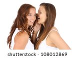 two smiling young girlfriends talking a secret over white - stock photo