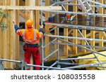 Construction worker in wooden house construction site - stock photo