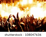 cheering crowd in front of bright yellow stage lights - stock photo