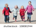 Children running at the beach - stock photo