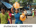 MUMBAI,INDIA-NOVEMBER 26:Woman carrying water on Nov.26, 2010 in Mumbai.In India women fetching water spend 150 million work days per year, equivalent to a national loss of income of 10 billion Rupees - stock photo