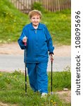 Active old woman (85 years old) nordic walking outdoors. - stock photo