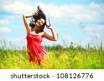 Happy beautiful woman dancing in meadow - stock photo