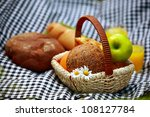 Basket with bread and fruits and juice on checked tablecloth - stock photo