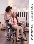 Small photo of Genuine care. Optimistic crippled girl using wheelchair while woman looking at her