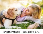 Stock photo beautiful senior woman with dog in spring nature 1081896173