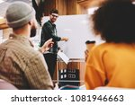Small photo of Successful male coach conducting seminar explaining information standing near white flipchart in university.Creative positive leader talking about business plan with students during workshop