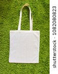 Small photo of Eco bag made of unpainted 100 cotton on a green artificial grass background. Top view. Mockup