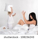 mother and daughter having fun with pillows on bed - stock photo