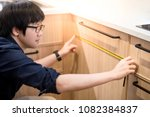 young asian man using tape... | Shutterstock . vector #1082384837