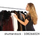 Attractive young woman choosing a fur coat from the hanger - stock photo