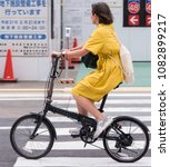 Small photo of TOKYO, JAPAN - MAY 1ST, 2018. Woman in yellow dress cycling a foldable bicycle in Shibuya street.