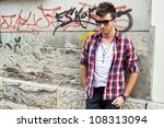 Man standing on tagged wall. - stock photo