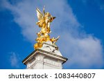 Small photo of London, UK - April 26, 2018: The gold Victoria Memorial Statue outside Buckingham Palace late in the day. The famous statue has been a focal piece of the Buckingham Palace since 1911.