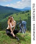 Small photo of Attractive sporty female backpacker with backpack and trekking sticks resting after travelling on the top of a hill, looking away, enjoying summer day in the mountains. Concept of active lifestyle