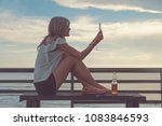 girl using cellphone on the... | Shutterstock . vector #1083846593