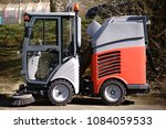 Small photo of The side view of a small street cleaning vehicle with brush and a driver's cab with all-round visibility.