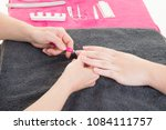 Small photo of Beautician looking through nail polishes in nailcare salon woman doing nail manicure